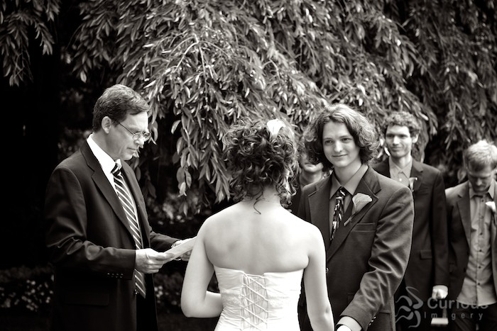 groom looking at bride during wedding ceremony in garden. black and white