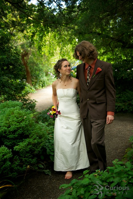 bride and groom walk through wooded path in garden