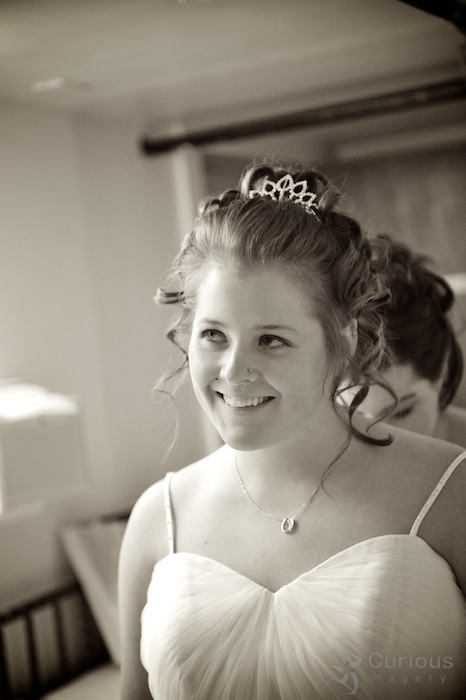 bride smiling and looking up. getting ready for wedding. sepia toned black and white