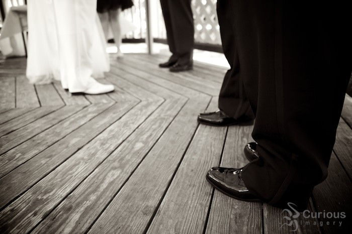 detail of groomsmen's shiny black shoes at wedding. sepia toned black and white