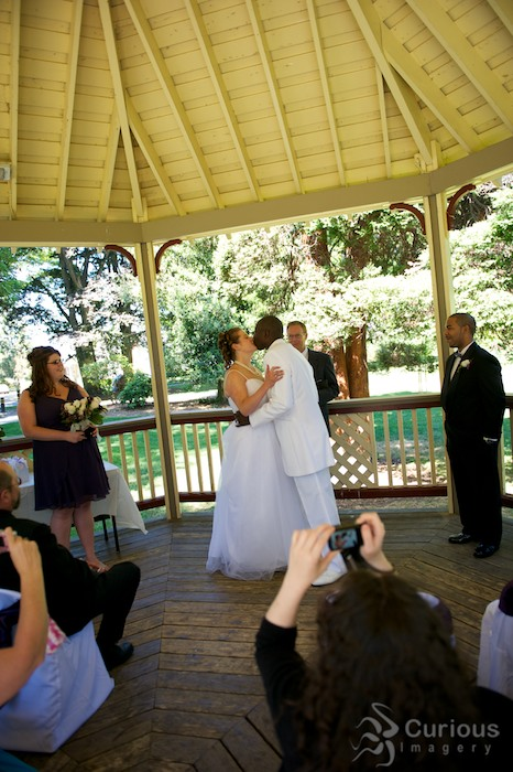 bride and groom kiss while audience takes pictures