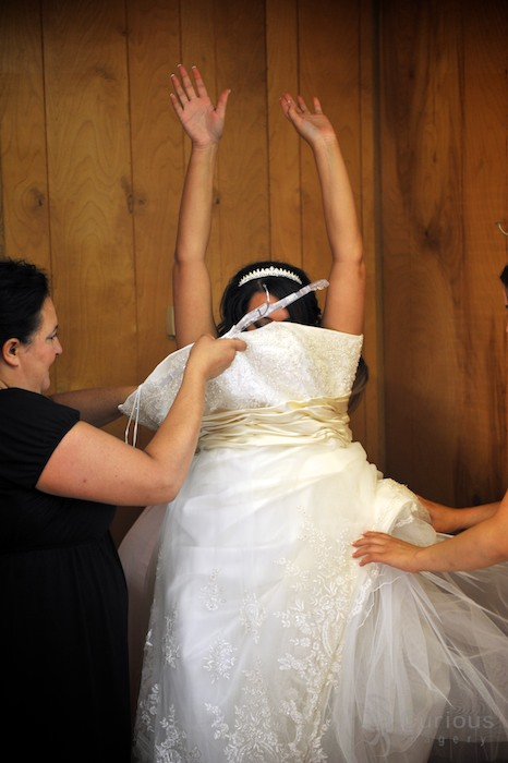 bride putting on wedding dress