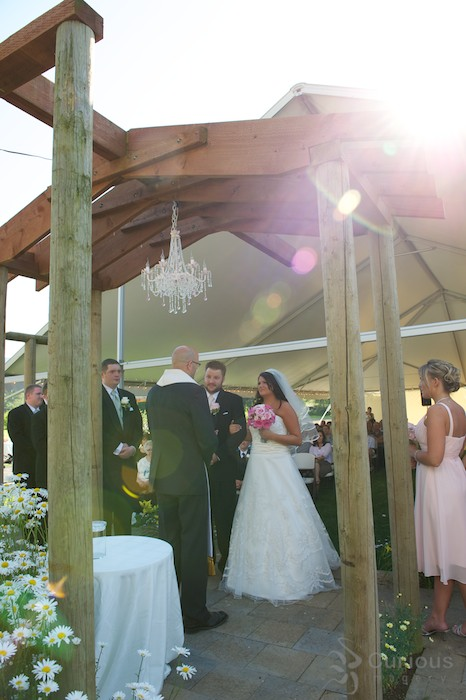 bride and groom getting married outside under arbor