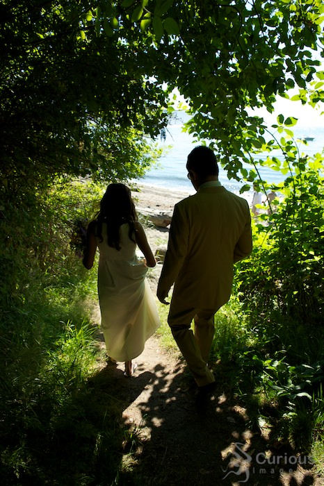bride and groom walk through tunnel of green down to beach