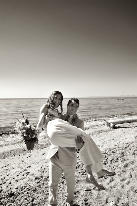 groom carrying bride at beach on lummi island near bellingham