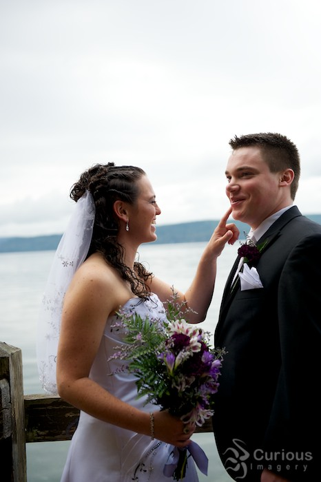 bride and groom by the ocean, joking and teasing each other. happy, outdoors, quirky
