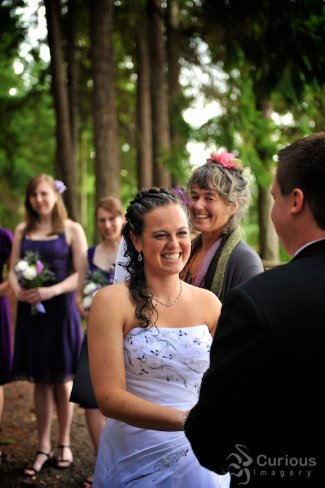 ecstatic bride smiles at groom during outdoor wedding ceremony. female officiant in background.