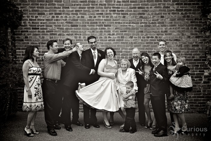 Goofy posed family wedding photo. Sepia toned, brick background.