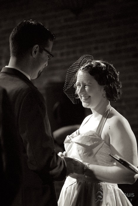 Bride and groom smile at each other during wedding ceremony. Telephoto, black and white.