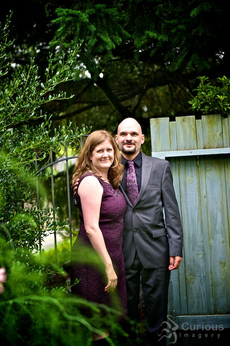 outdoor portrait of newly married couple, by garden gate