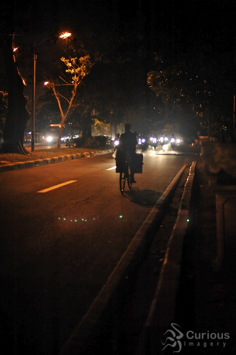 silhouette of man on bicycle on road in Jakarta