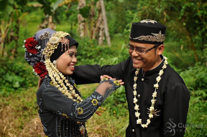 Indonesian bride and groom joke and lauch during wedding portraits