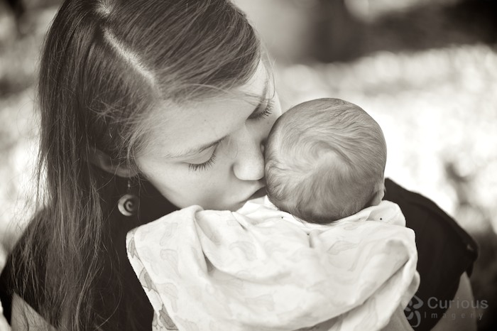 mother gently kissing newborn baby boy. B&W photo