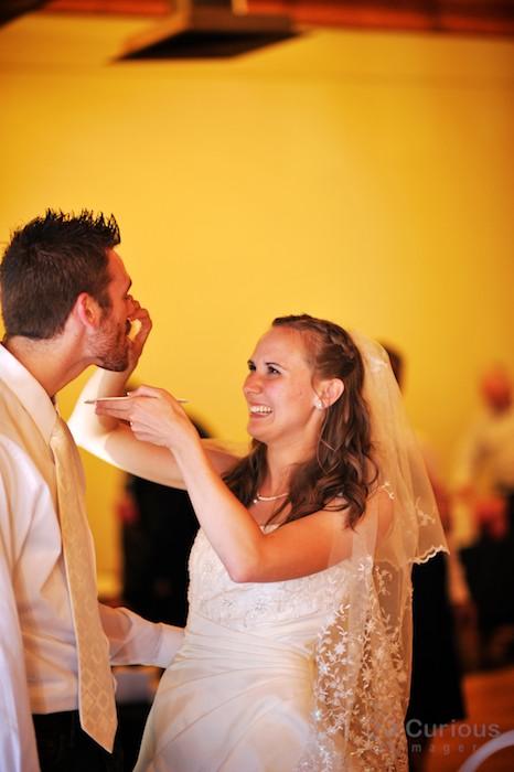 Bride feeds groom a piece of cake.
