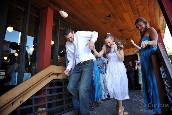 Bride and groom exit to getaway vehicle.